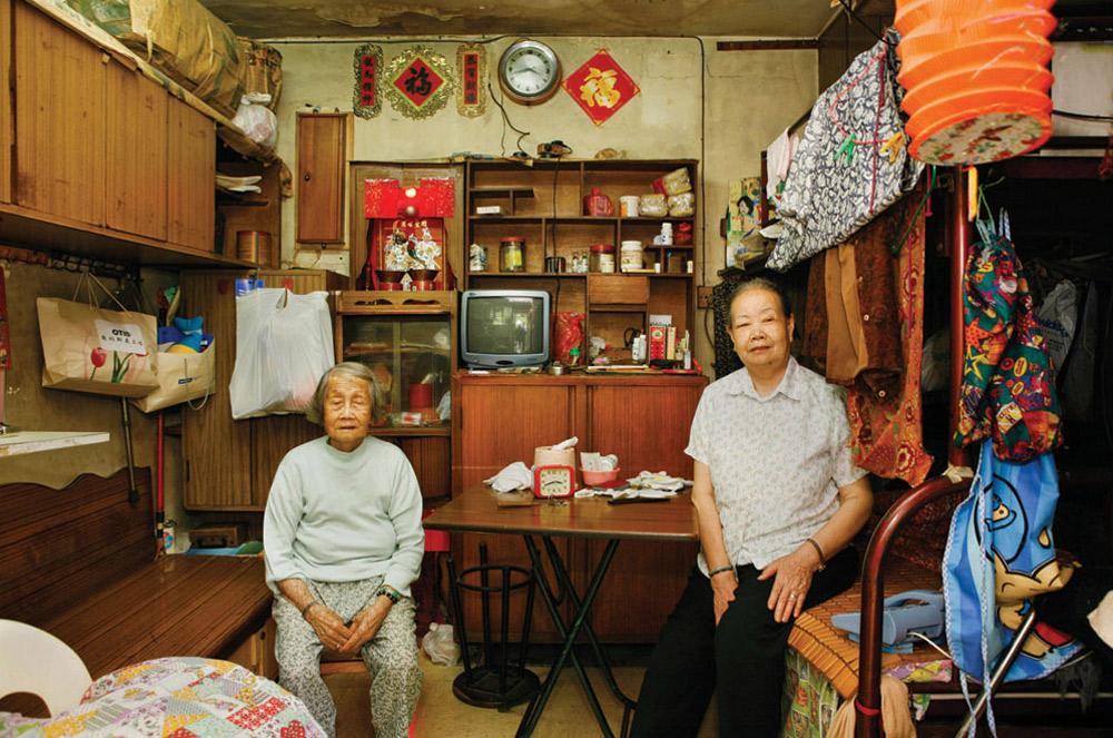 12. 82-летняя Вонг Юнг Нуи (слева) прожила здесь 30 лет. Она работает посудомойкой в ресторане. Что больше всего нравится  в этом месте? «Низкая аренда и соседи, которые всегда помогут». (Michael Wolf/ New York Times Lens)