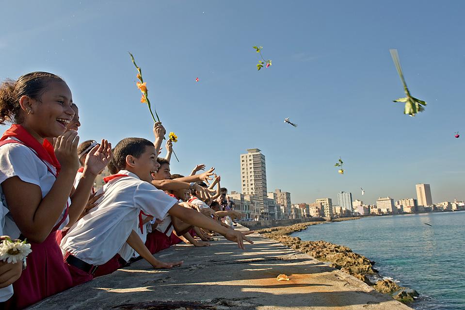 7) Кубинские школьники бросают цветы в море на набережной Малекон в Гаване во время 50-й годовщины исчезновения кубинского революционера Камило Сьенфуэгоса, который пропал в 1959 году во время авиакатастрофы над морем. (Adalberto Roque/AFP/Getty Images)