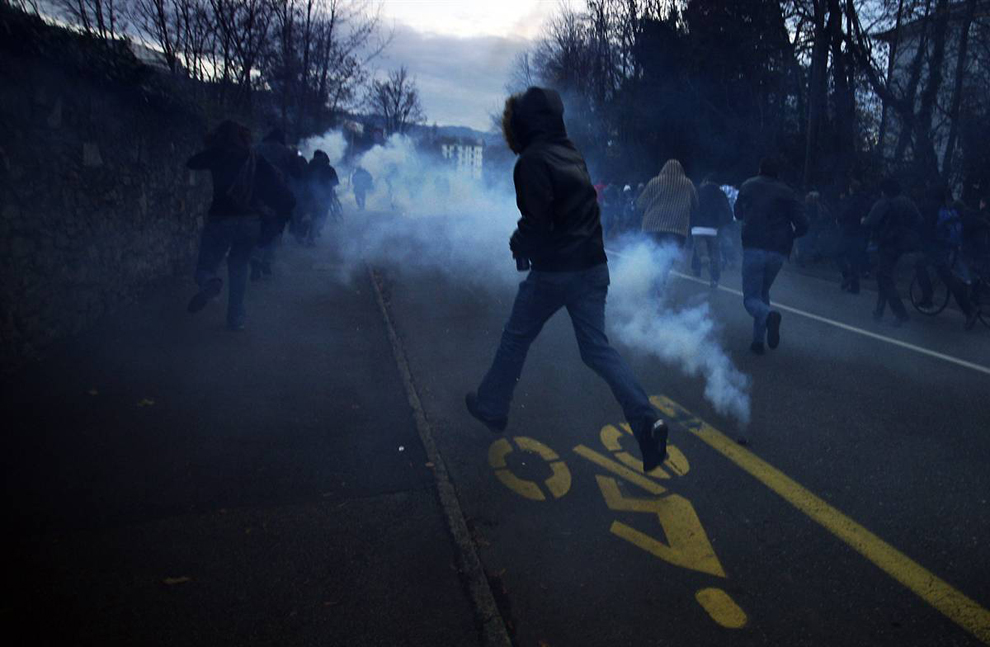 1) Участники акции протеста убегают от слезоточивого газа. Полиция вынуждена применить резиновые пули и слезоточивый газ для разгона агрессивных демонстрантов. (Valentin Flauraud / Reuters)