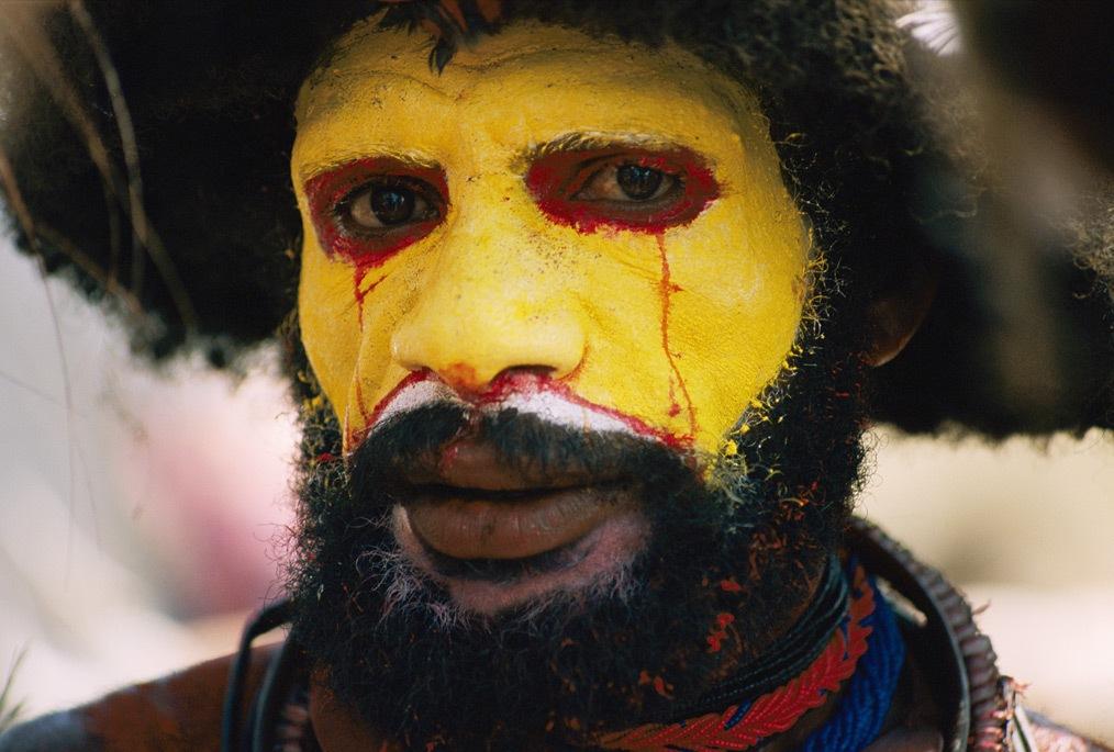 7. Красные капли пота бегут по разрисованному желтым лицу хули в Папуа Новая Гвинея. В его изысканный костюм, надетый по случаю церемониального праздника под названием синг-синг, также входит эффектный парик из человеческих волос. (Jodi Cobb)