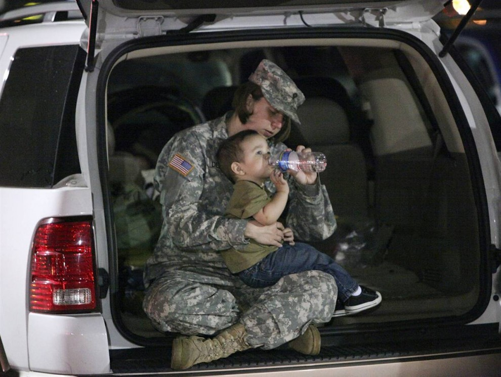 7. Специалист армии США Джеми Делое сидит с сыном своих друзей и ждет, пока ее пустят на военную базу в Форт-Худ в четверг. (Edward A. Ornelas / Zuma Press)
