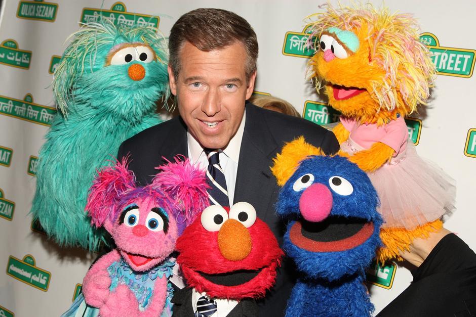 8. 27 мая 2009: ведущих вечерних новостей на канале NBC Брайан Уильямс позирует с куклами «Улицы Сезам» на 7-ом гала-концерте в Нью-Йорке.