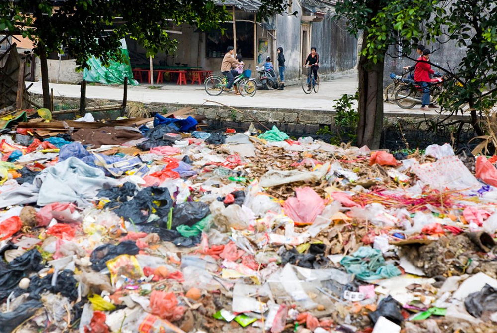 8) Кучи мусора у обочины дороги в Гуйюй.