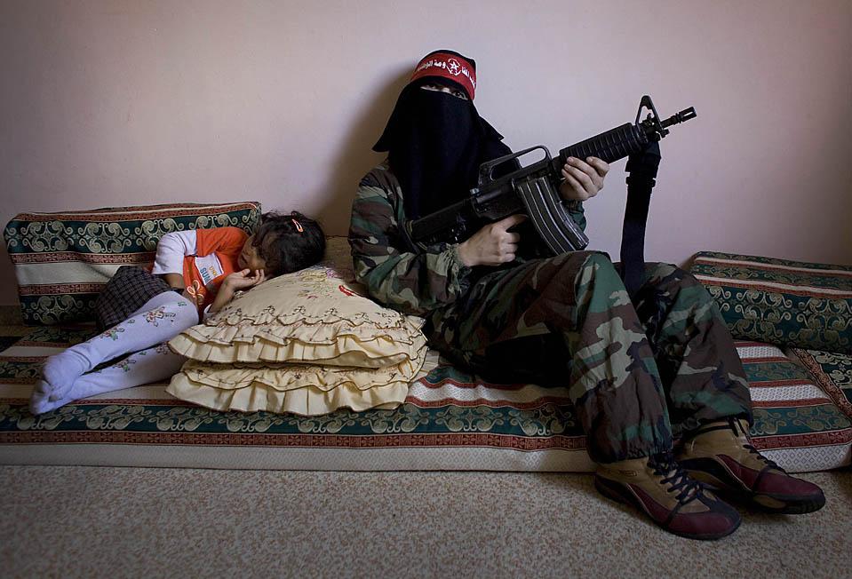 8) Омм Ахмед, справа, женщина-боевик из Демократического фронта по освобождению Палестины позирует фотографу в доме своего товарища по оружию в секторе Газа. Основанная в 1969 году, ДФОП насчитывает около 40 женщин, проходящих специальную подготовку, которая началось шесть месяцев назад в качестве ответа на январское наступление Израиля. (Tara Todras-Whitehill/Associated Press)
