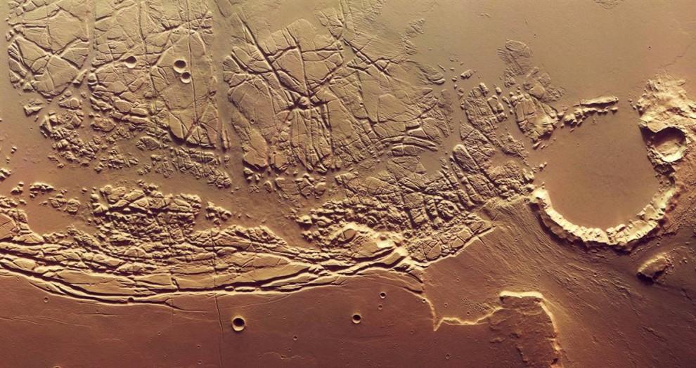 8. Эта мозаика снимков, сделанных орбитальным аппаратом «Mars Express» и опубликованных 6 ноября, представляет великолепный вид хаотичной территории на границе между долинами Касэй и Сакра Фоссэ. Эта территория равняется половине площади Нидерландов. След кратера справа был, скорее всего, оставлен еще давно проточными водами. (ESA/DLR/FU Berlin)