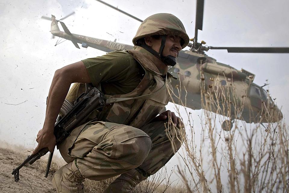 8) Пакистанский солдат присел во время взлета вертолета пакистанской армии на вершине горы Кунда, Пакистан. Пакистанская армия сейчас занимается зачисткой территории с целью уничтожения двух основных баз талибов в южной провинции Вазиристан. (Nicolas Asfouri / Reuters)