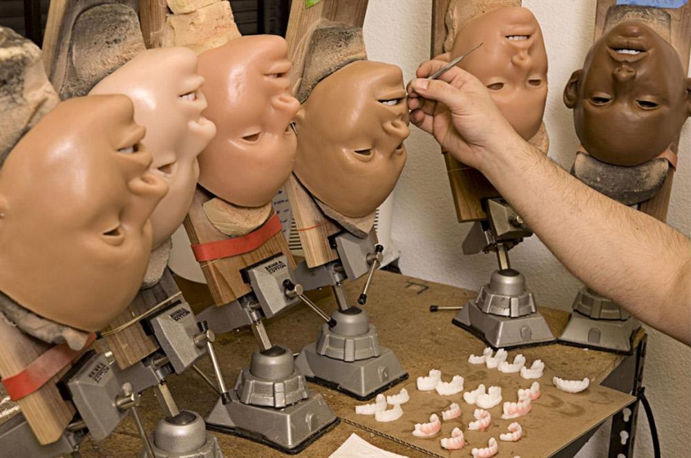 8. Дерек Транк в процессе нанесения косметики на лицо куклы.