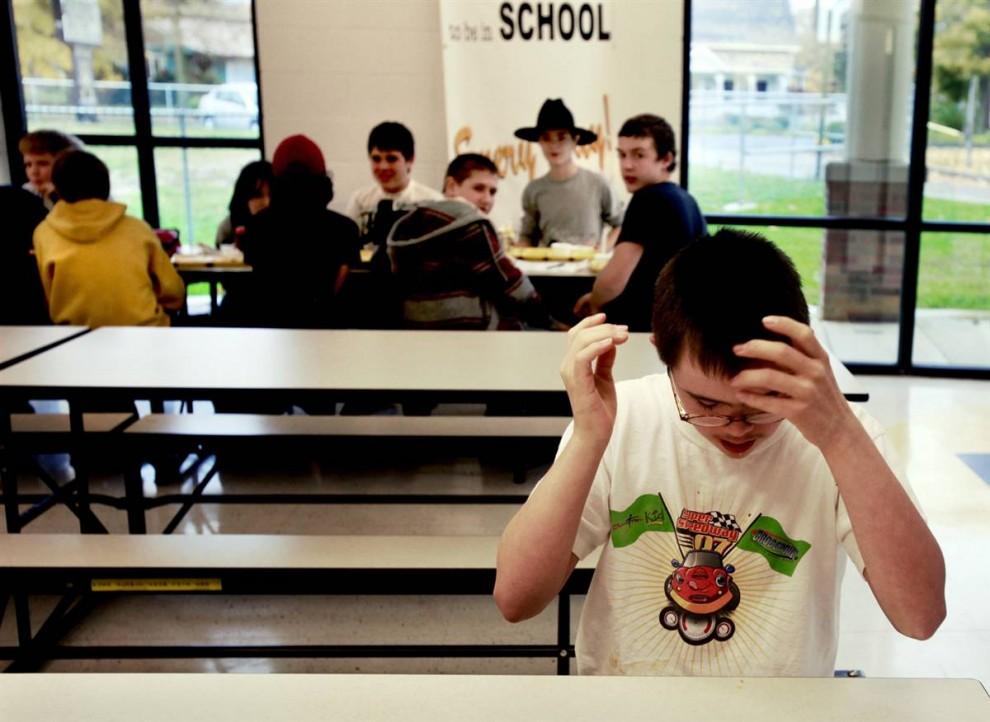 9. 14-летний Уильям Уинчестер с синдромом Дауна сидит в столовой средней школы Мюррея после ланча. Уильям в восьмом классе, он проходит специальную образовательную программу. Программа включает в себя как обычные занятия, так и спецобразование. Уильяма знают многие школьники, так как он начал заниматься по этой программе еще в начальной школе. (Sara Naomi Lewkowicz/2009 Mountain Workshops)