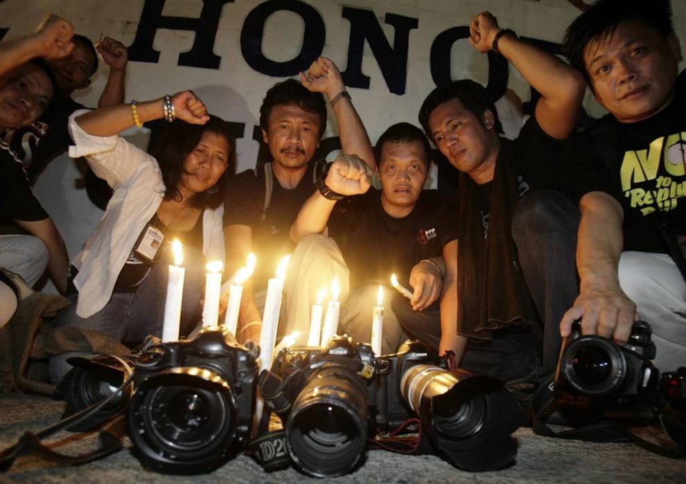 9) Фотографы поставили свечи в память жертв предвыборной бойни в провинции Магинданао, в ходе акции протеста у здания Национальной штаб-квартиры Филиппин в Маниле.