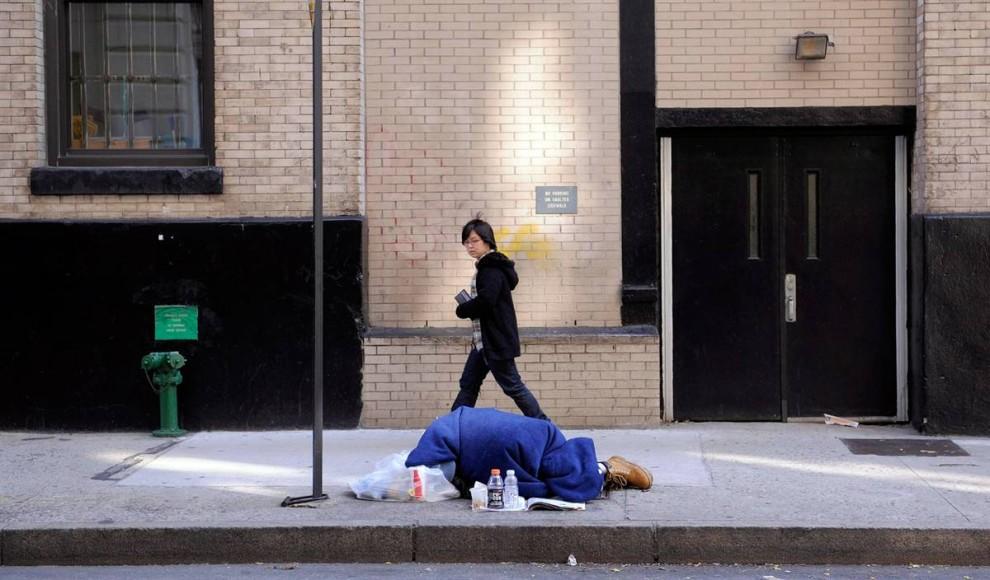 10. Прохожий идет мимо спящего на улице человека в Нью-Йорке. Организации по борьбе с проблемой бездомности сообщают, что из-за экономического кризиса число бездомных резко увеличилось. (Justin Lane / EPA)