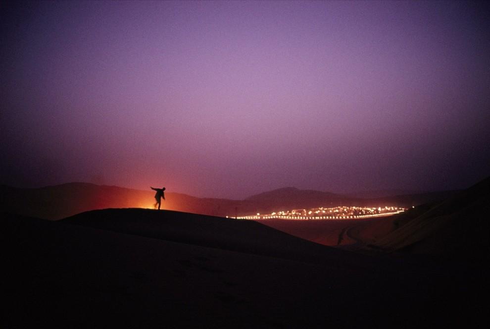 10. Человек танцует на песчаной дюне на фоне месторождения нефти Шайбах, придавшем небу Саудовской Аравии пурпурный оттенок. Саудовская Аравия контролирует примерно четверть всех мировых запасов нефти. (Reza)