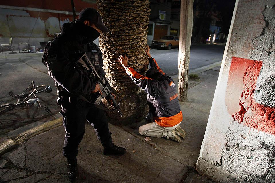 10) Федеральные полицейские обыскивают человека, подозреваемого в перевозке оружия и наркотиков во время антинаркотической операции в мексиканском Екатепек. (Daniel Aguilar/Reuters)
