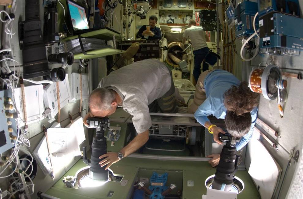 10. Астронавты НАСА Джеффри Уильямс и Николь Стотт направляют свои камеры в окна Международной космической станции, чтобы сделать фотографии космического корабля «Атлантис» в момент его приближения 18 ноября. Снимки нужны для анализа любых доказательств повреждений шаттла во время его восхождения на орбиту. (NASA)