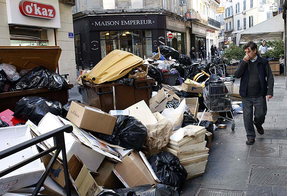 6) Человек проходит мимо кучи мусора в Марселе, на юге Франции на седьмой день забастовки сборщиков мусора в городе. (Philippe Laurenson/Reuters)