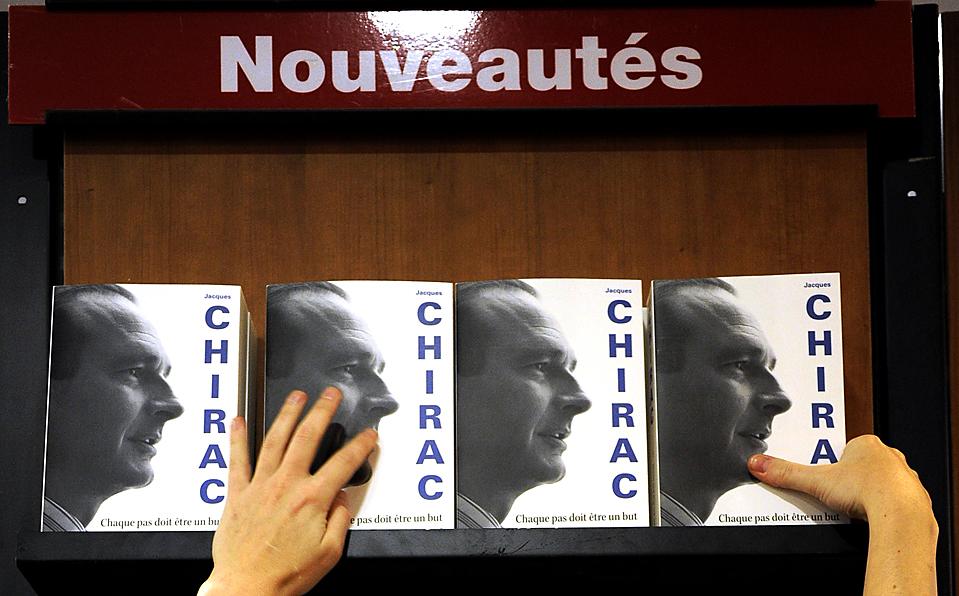 """13) Сотрудница книжного магазина в Париже выставляет экземпляры мемуаров бывшего президента Франции Жака Ширака. Самая ожидаемая книжная новика Франции на этой неделе называется """"Каждый шаг должен быть целью"""". (Jacky Naegelen/Reuters)"""