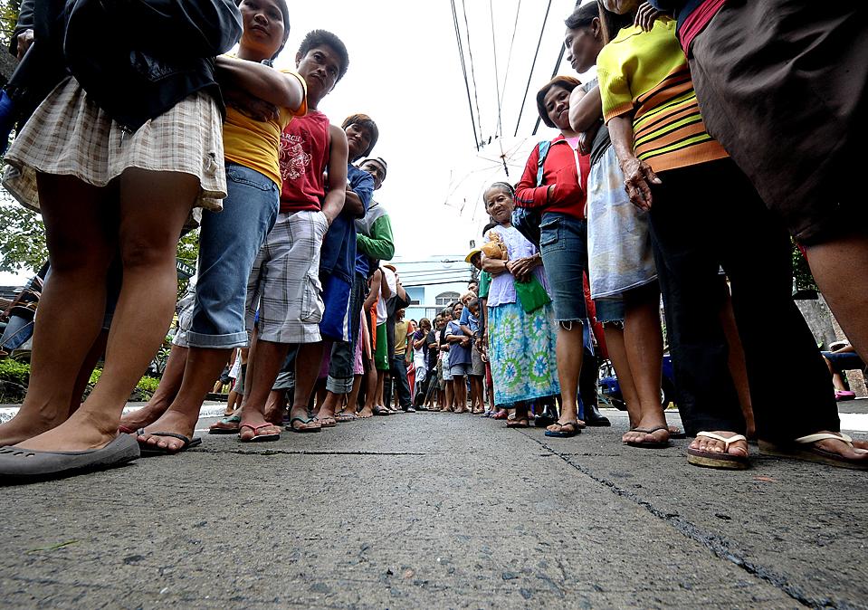 16) Пострадавшие от наводнения выстроились в очередь, чтобы получить гуманитарную помощь ООН. Снимок сделан в Маниле, Филиппины в четверг. Из-за тропических штормов и тайфунов, которые один за другим проходили через этот регион в октябре, погибло около 1000 человек, уничтожены большие участки сельскохозяйственных угодий и затоплена большая часть столицы. (Jay Directo/Agence France-Presse/Getty Images)