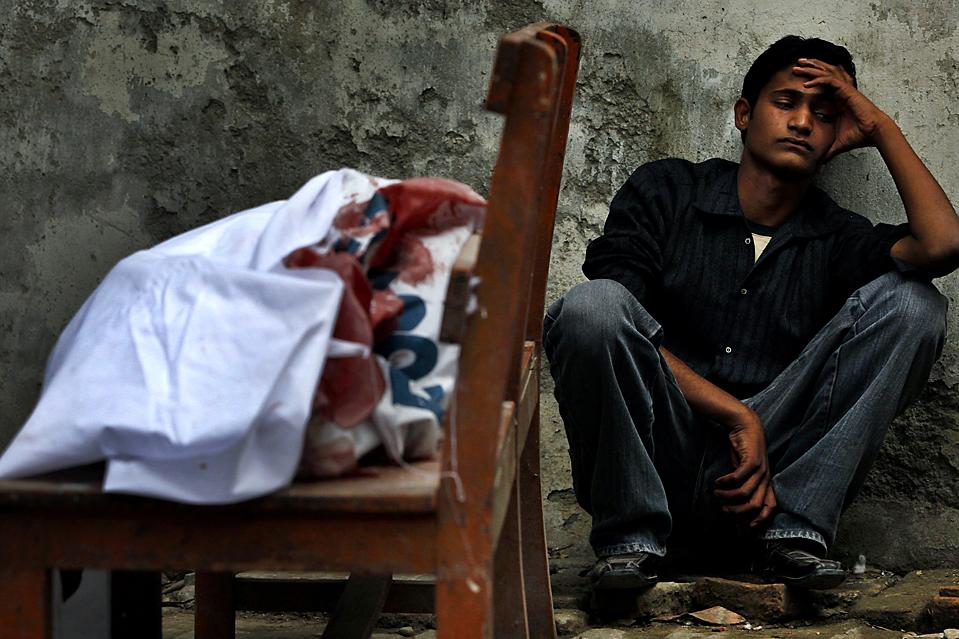 4) Аджмал сидит рядом с останками своего брата в морге больницы под Исламабадом. В результате нападения террориста-смертника, который взорвал себя у здания банка в пакистанском городе Равалпинди, погибли, по меньшей мере, 34 человек. (Faisal Mahmood/Reuters)