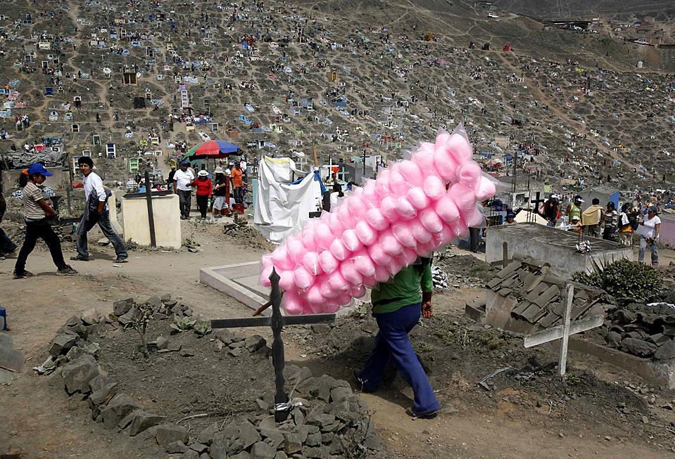 """7) Уличный торговец рядом с могилами в """"День мертвых"""" на окраинах Лимы, Перу. Каждый год тысячи людей в Перу и других странах посещают кладбища, чтобы почтить память своих умерших родных и близких. (Mariana Bazo/Reuters)"""