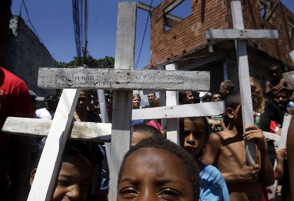 8) Дети несут кресты во время акции протеста против насилия, которая прошла в понедельник трущобах Рио-де-Жанейро под называнием Мандела. Акция прошла после того, как на прошлой неделе в ходе перестрелки между полицейскими и наркоторговцами погиб студент. (Ricardo Moraes/Reuters)
