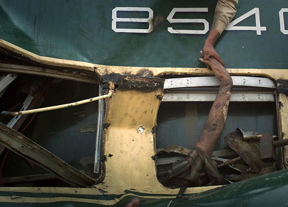 5) Участвующий в спасательных работах доброволец хватает руку пострадавшего в столкновении поездов в Карачи, Пакистан. Пассажирский поезд врезался в грузовой, причиной чего, вероятно стало то, что машинист пропустил сигнал к остановке. В результате столкновения погибли, по меньшей мере 10 человек, включая младенца, сообщают официальные источники. Были ранены более 30 человек. (Adrees Latif/Reuters)
