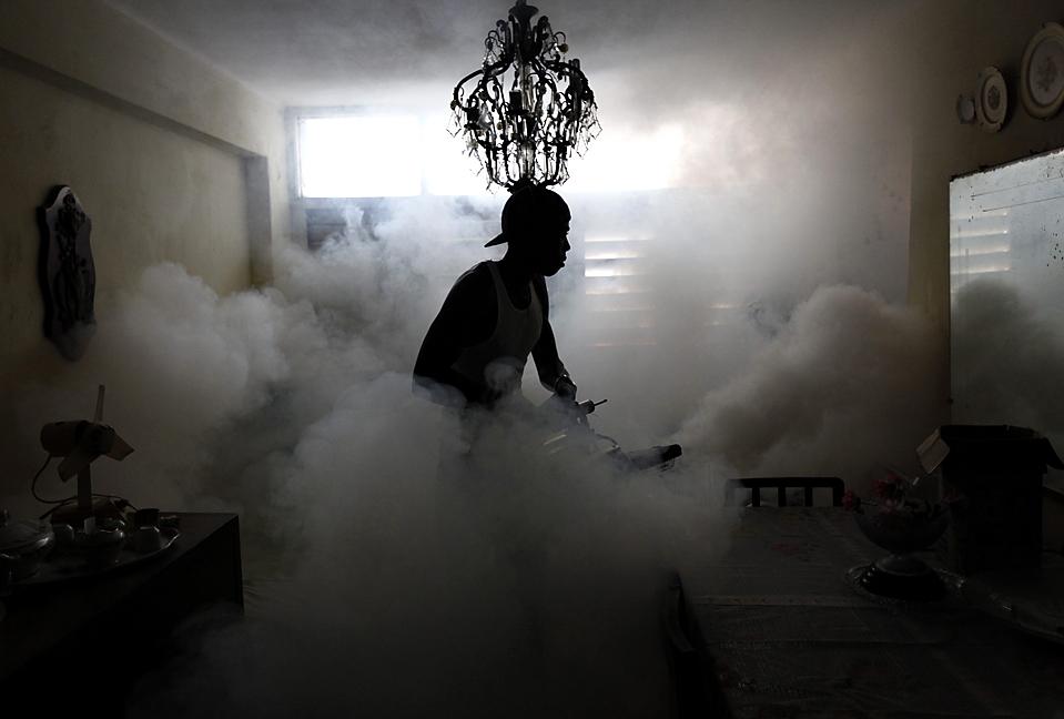 9) Работник санитарной службы распыляет специальное вещество внутри дома в Гаване, чтобы остановить распространение лихорадки денге, передающегося комарами. (Desmond Boylan/Reuters)