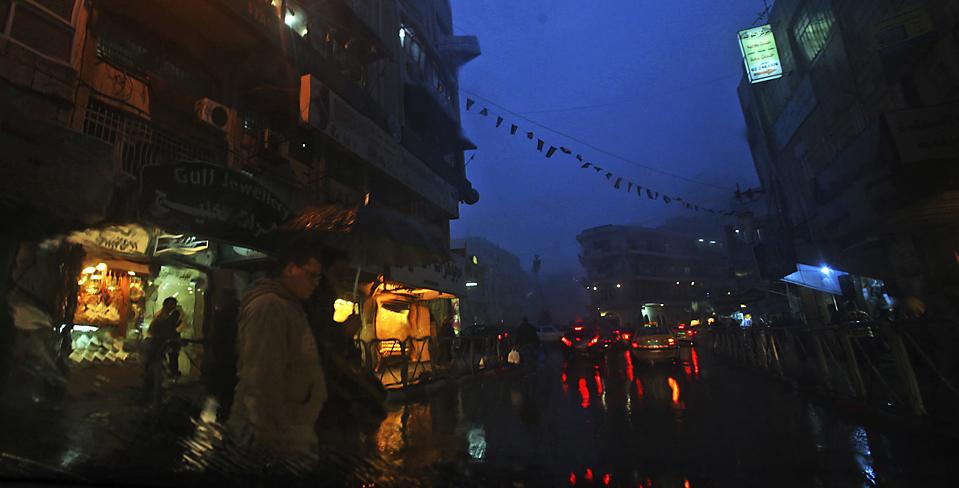 10) Палестинцы во время сильного дождя в Рамалле, на Западном берегу реки Иордан. (Muhammed Muheisen/Associated Press)
