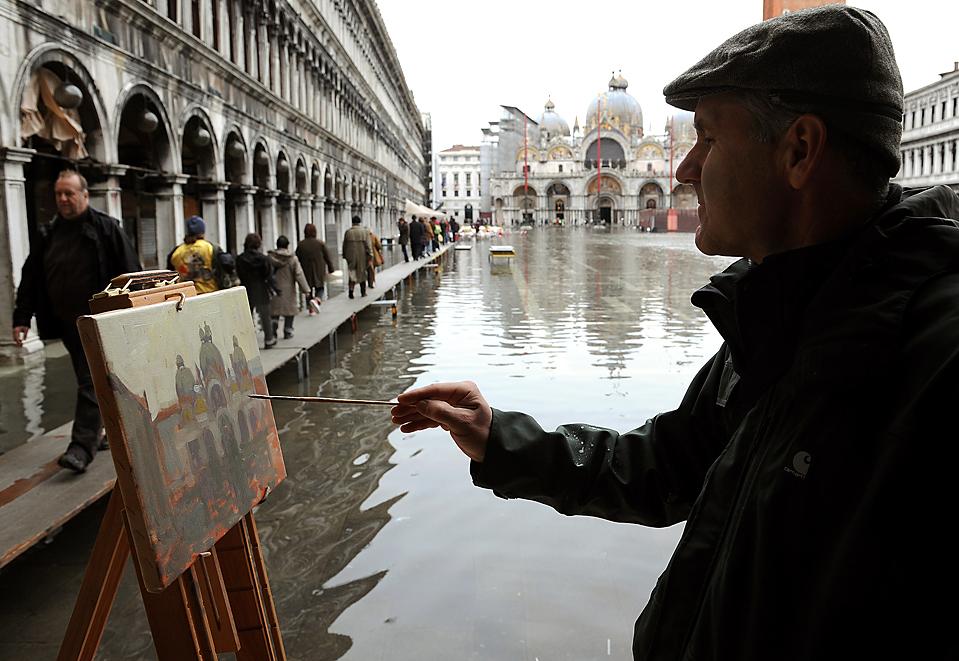 13) Мужчина рисует картину на затопленной площади Святого Марка в Венеции. (Alberto Pizzoli/Agence France-Presse/Getty Images)