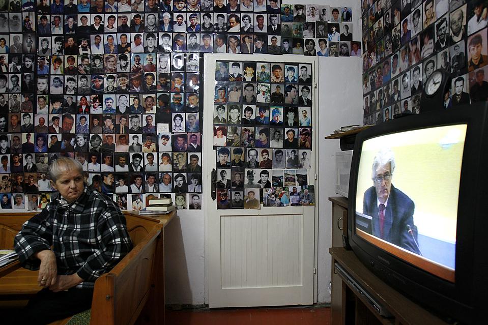 6) 64-летний Хаджра Катик, боснийский мусульман из Сребреницы, смотрит судебный процесс по делу Радована Караджича в Тузле, Босния, окруженный фотографиями жертв резни в Сребренице 1995 года. Караджичу выдвинуты обвинения по 11 пунктам в военных преступлениях, в том числе два – обвинения в геноциде. (Amel Emric/Associated Press)