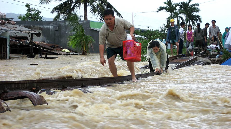 11) Люди идут по затопленным железнодорожным путям в провинции Бинь Динь, Вьетнам,. Число погибших от тропического шторма Миринаэ увеличилось до 91 во Вьетнаме, в среду, поскольку власти активизировали поисково-спасательных операций в центральном регионе страны. (Thai Son/Vietnam News Agency/Associated Press)