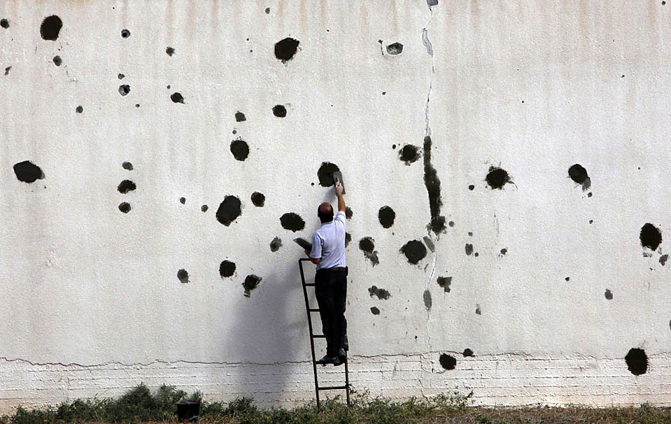 11) Палестинец замазывает следы от пуль на заводской стене в северной части сектора Газа. Здание было повреждено во время трехнедельного наступления израильтян в декабре прошлого года. (Yannis Behrakis/Reuters)