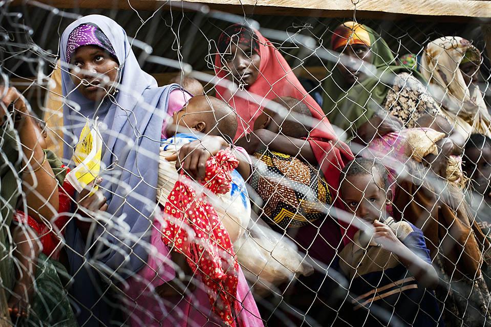 4) Сомалийские женщины и дети в ожидании раздачи пайков в Центре питания в Дадаабе, Кения. Дадааба представляет собой крупнейший в Африке лагерь беженцев, где проживают более 250 тысяч людей, бежавших из  Сомали из-за продолжающегося военного конфликта. (Kate Holt/AFP/Getty Images)