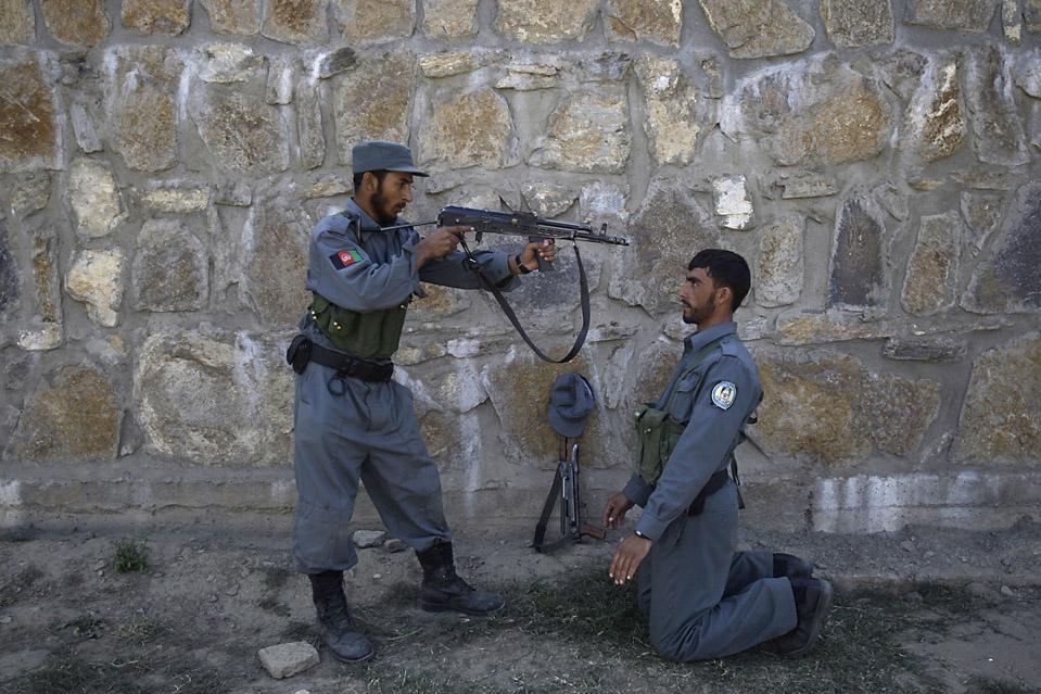 Полицейские афганской национальной полиции принимают участие в учениях вместе с армией США на блокпосту в долине Печ. Человек, стоящий на коленях, учится разоружать нападающего. (David Guttenfelder/Associated Press)