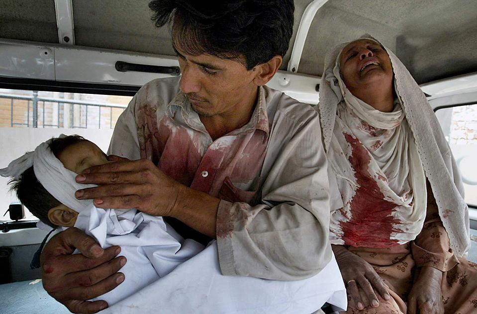 9) Мужчина держит своего сына, который был убит в результате теракта, а рядом рыдает бабушка мальчика. Снимок сделан внутри фургона одной из больниц в Пешаваре, Пакистан, в воскресенье. Террорист-смертник взорвал себя на рынке, в результате чего был убит выступающий против талибов городской председатель и, по меньшей мере, еще 11 человек. (Mohammed Iqbal/Associated Press)