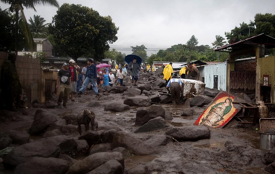 10) Жители пробираются по затопленной улице возле образа Богоматери Гваделупе в Верапасе, Сальвадор. Десятки человек пропали без вести в результате оползня, который обрушился на город. Из-за наводнений и оползней, в стране погибли, по меньшей мере, 134 человек. (Edgar Romero/Associated Press)