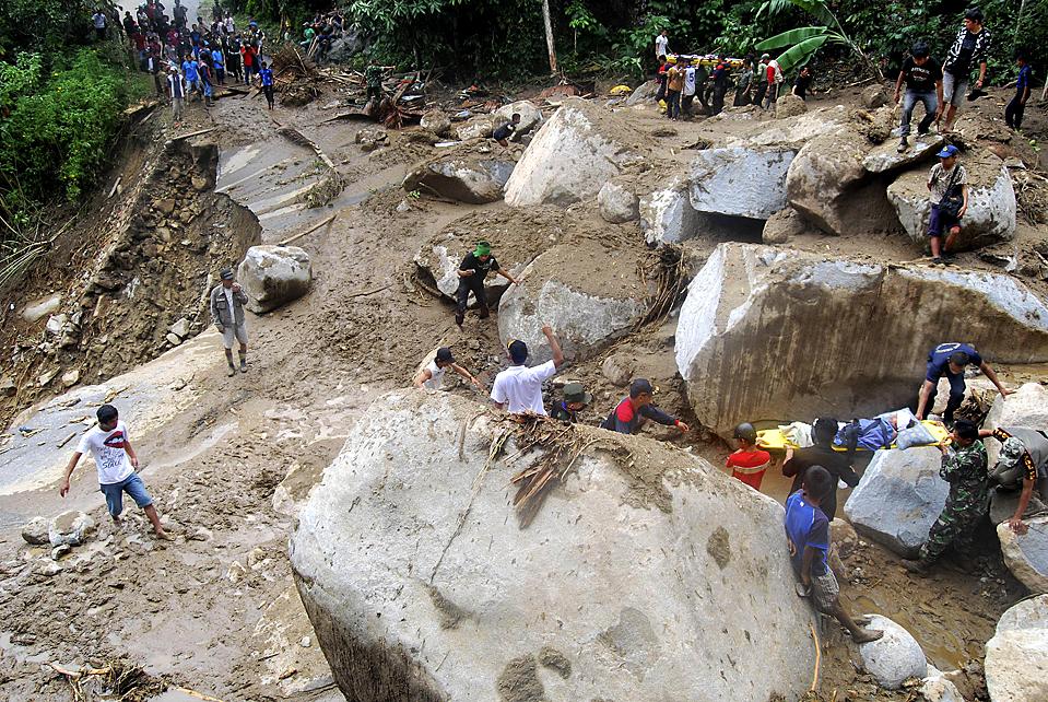 11) Спасатели несут пострадавших от оползней в деревне Баттанг Барат, Южный Сулавеси, Индонезия. (Roel/Associated Press)