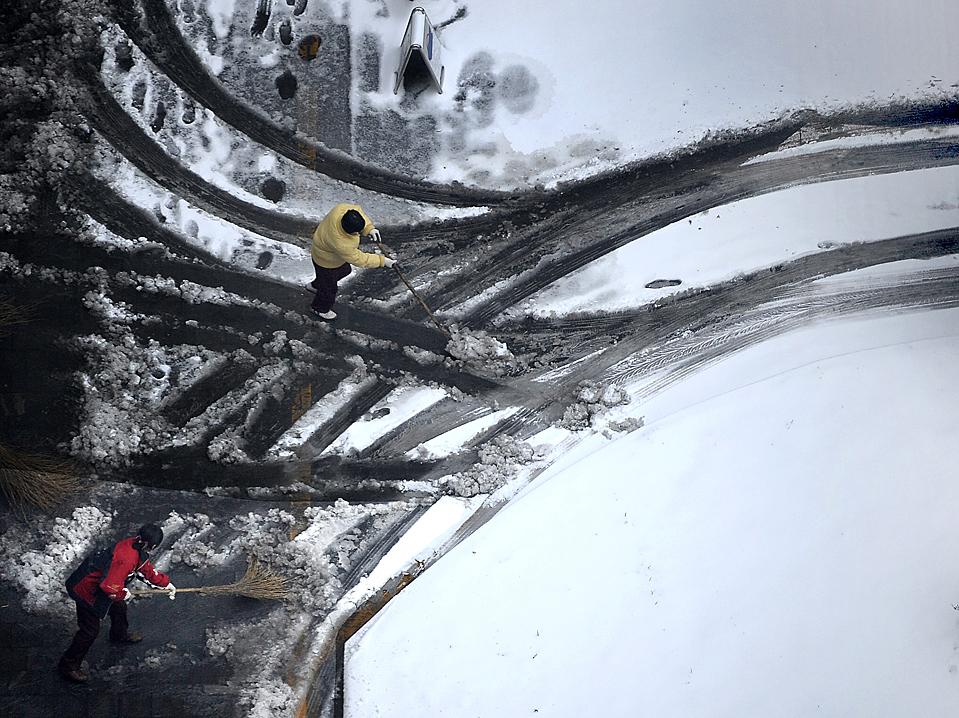 1) Люди расчищают заснеженный подъезд у своих квартир в Пекине. Авиарейсы были отменены и задержаны после того, как вторая за эту осень метель засыпала снегом столицу Китая. (Andy Wong/Associated Press)
