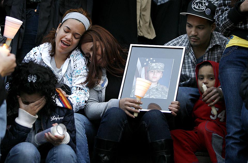 4) Родственники погибшей рядовой армии США, 21-летней Франчески Велес, слушают музыку во время поминок. Франческа была беременна, когда ее застрелил майор Нидал Хасан Малик в Форт-Худ в Техасе, на прошлой неделе. Кроме нее погибло еще 13 человек.  (John Smierciak/Associated Press)