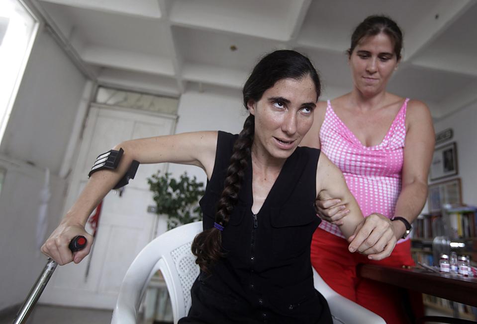 13) Йоани Санчес, слева у себя дома в Гаване. Как утверждает девушка, полицейские агенты остановили ее и двух ее друзей в Гаване. Санчес, которая является блоггером, выступающим в оппозиции кубинскому правительству, заявила, полицейские избили ее и оттаскали за волосы. Государственный департамент США осудил нападение на кубинских блоггеров. (Enrique De La Osa/Reuters)