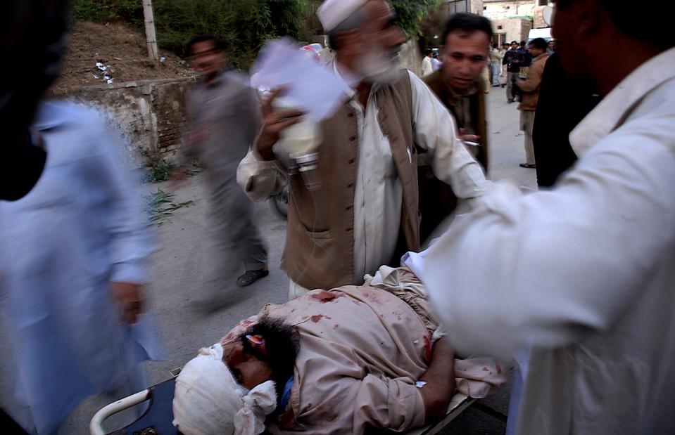 14) Жертвы взрыва автомобиля доставлены в госпиталь в Пешаваре, Пакистан. Бомба взорвалась на людном рынке, убив, по меньшей мере, 24 человек. (Mohammad Iqbal/Associated Press)