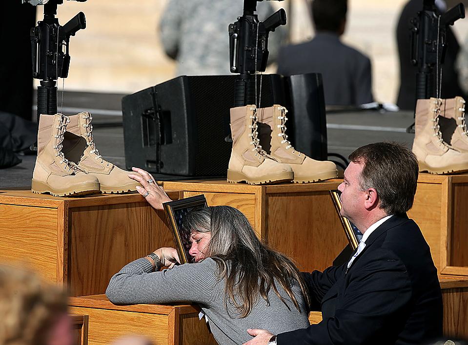 15) Женщина с фотографией своего погибшего родственника, одного из 13-ти погибших на прошлой неделе на военной базе в Форт Худ, штат Техас. (Rodolfo Gonzalez/Associated Press)