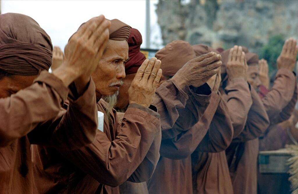 11. Одетые в коричневое, буддистские монахи молятся за мир во Вьетнаме. В 1950-ых, 60-ых и 7-ых годах война разделила вьетнамский народ. (W.E. Garrett)