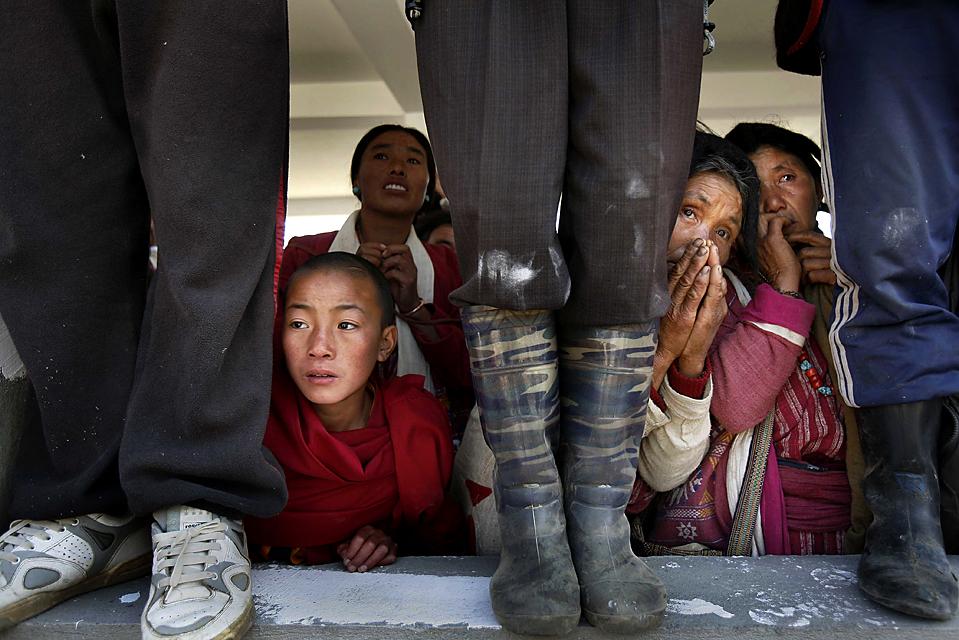 6) Буддисты выглядывают, чтобы увидеть Далай-ламу, который идет от вертолетной площадки после серии публичных мероприятий в городе Таванг, штат Аруначал-Прадеш, Индия. (Manish Swarup/Associated Press)