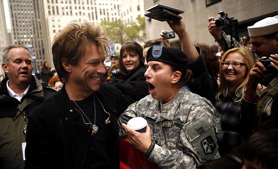 7) Музыкант Джон Бон Джови обнимает военного специалиста армии Синди Паулу перед выступлением на шоу телеканала NBC «Today» в Рокфеллер-центре в Нью-Йорке. (Jason DeCrow/Associated Press)
