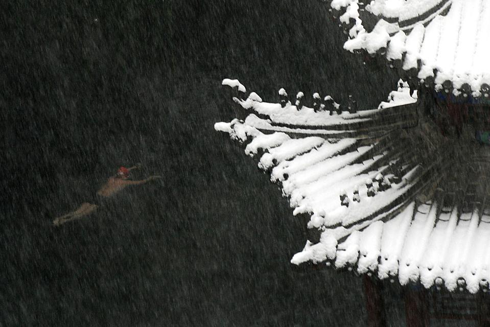 8) Покрытая снегом крыша видна на фоне озера, в котором купается человек. Снимок сделан в городе Цзинань, провинция Шаньдун, Китай. (Reuters)
