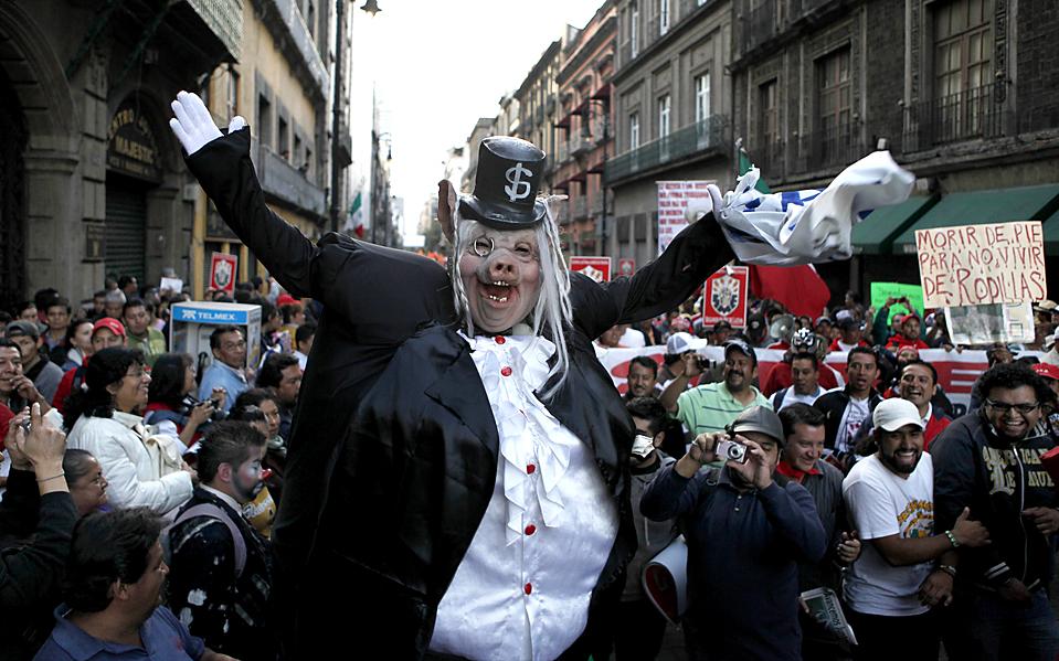 12) Одетый в костюм свиньи участник акции протеста против решения правительства о роспуске государственной энергетической компании Luz y Fuerza в Мехико. Президент Фелипе Кальдерон мотивирует решение о закрытии неэффективностью производства и дефицитом бюджета. (Eduardo Verdugo/Associated Press)