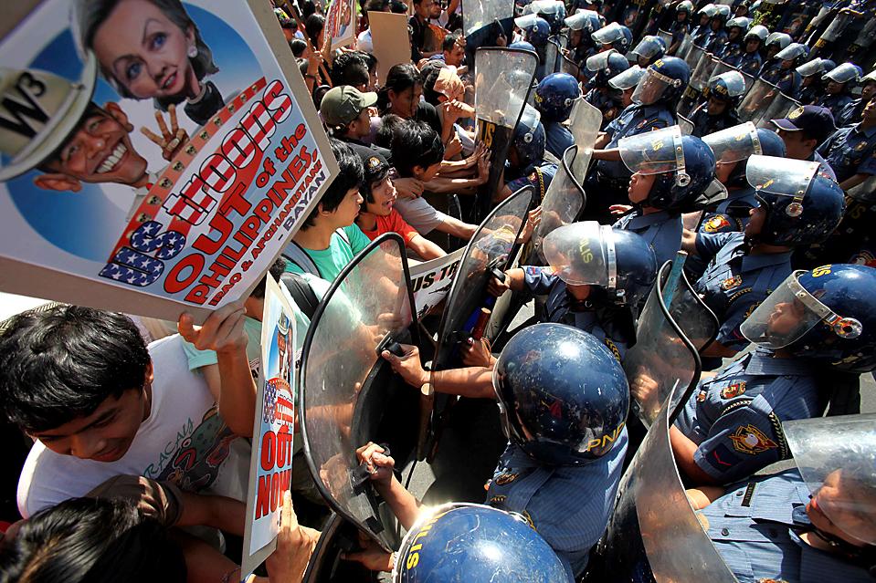 """13) Протестующие во время стычки с полицией у посольства США в Маниле во время визита госсекретаря США Хиллари Клинтон. Клинтон заявила, что США поддерживают продолжающуюся борьбу Филиппин по искоренению """"Аль-Каиды». (Bullit Маркес/Associated Press)"""
