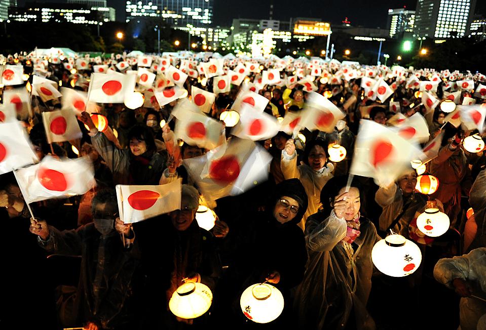 15) Десятки тысяч людей размахивают японскими флагами и фонарями, во время публичного выступления императора Акихито и императрицы Митико в императорском дворце в Токио, во время празднования 20-летия коронации императора. (Shuji Kajiyama/Associated Press)
