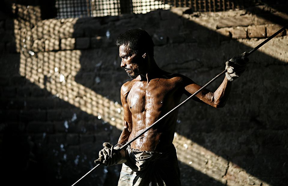 2) Человек работает на производстве алюминия в Дакке, Бангладеш. Персонал предприятия составляет около 15 человек, которые зачастую работают по 12 часов в день, менее чем за $ 2 в день. (Andrew Biraj/Reuters)
