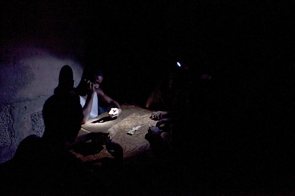 3) Люди играют в домино в свете фонарика в Порт-о-Пренс, Гаити. В большинстве городов в Гаити электричество дают только на несколько часов в день из-за недостаточного производства электроэнергии. (Ramon Espinosa/Associated Press)