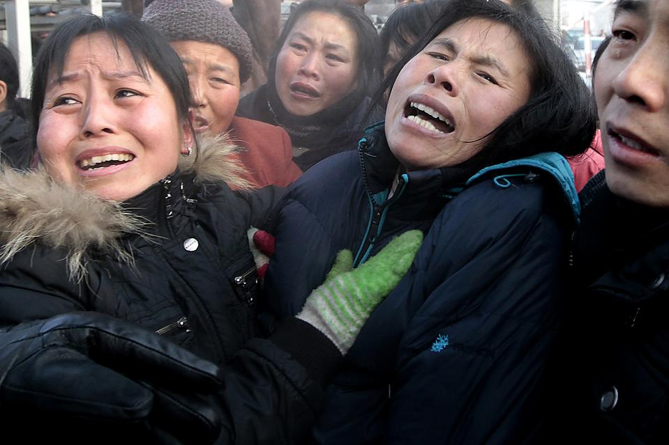 15) Родственники оплакивают шахтеров погибших на шахте Ксингксинг Хэган в китайской провинции Хэйлунцзян. В результате взрыва на шахте погибли 104 человека. Правительство говорит, что под землей в целях увеличения производства находилось одновременно слишком много шахтеров. (Aly Song/Reuters)